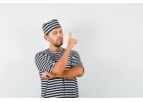 年轻的男性戴着条纹T恤帽子指了指看起来_13191354
