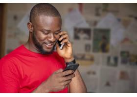 年轻的非洲男性一边打电话一边在房间里使_13361786