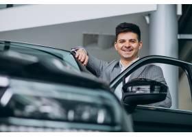 年轻英俊的商人在汽车展厅选车_6190345