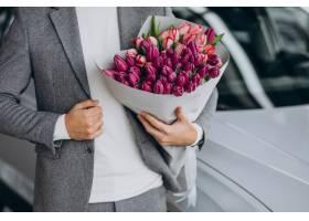 年轻英俊的商人送来一束美丽的鲜花_7377598