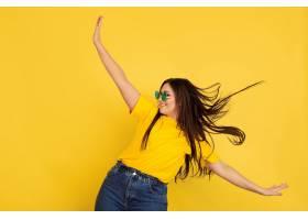很有灵感地戴着墨镜跳舞黄墙上的高加索女_12837959