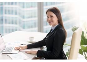 微笑开朗的年轻女商人拿着笔记本电脑在办公_3938483