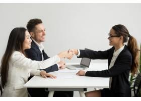 微笑的不同类型的女商人在小组会议上握手_3952578