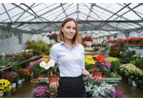 微笑的企业主站在她的苗圃里手里拿着温室_11179342