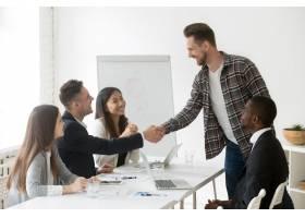 微笑的商人在小组会议上握手欢迎新合作伙伴_3939774