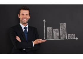 微笑的商人在黑板上展示图表_10676652