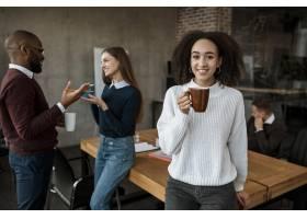 微笑的女人在办公室会议上拿着咖啡杯摆姿势_12065609