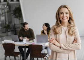 微笑的女人在她的同事旁边摆姿势的肖像_12142790