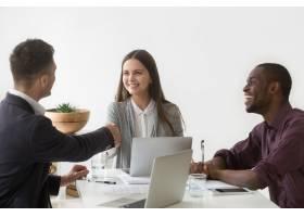 微笑的女商人在小组会议上与男合伙人握手_3939784