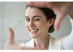 微笑的女子做相框手势的特写_999213