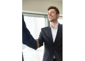 微笑的年轻商人穿着黑色西装握着男性的手_3955610