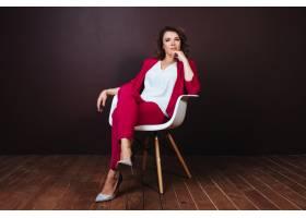 微笑的年轻女商人在黑暗的背景下坐在办公椅_2455551