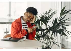 微笑的年轻女商人坐在办公室里的肖像_13319938