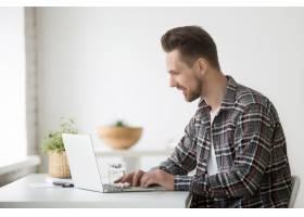 微笑的男子自由职业者在笔记本电脑上工作_3939758
