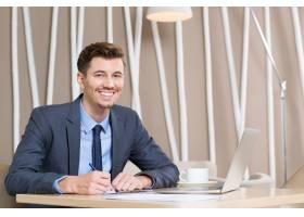 快乐的成年商人在办公室的办公桌前工作_999312