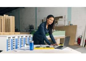 快乐的非裔美国女士带着笔记本电脑和桌子上_3706675