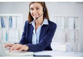 微笑的秘书在笔记本电脑上打字_865251