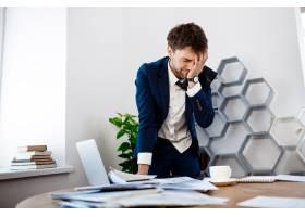 心烦意乱的年轻商人站在工作场所办公室背_7855279