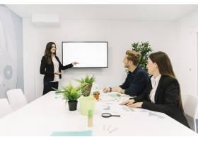 快乐的女商人在商务会议上向她的合作伙伴做_2524067
