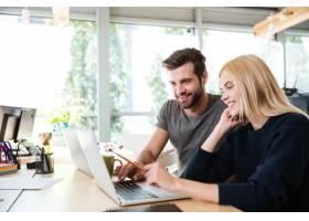 快乐的年轻同事坐在办公室里使用笔记本电脑_8078182