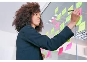 成功的漂亮女商人用记号笔在贴纸上写字深_9650711