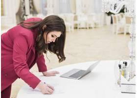 宴会厅里的活动经理在纸上写字_4191564
