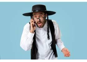 工作室里一位年轻的正统犹太男子拿着手机的_13340438