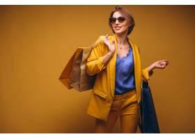 工作室里拿着购物袋的女子被孤立在黄色背景_4410843