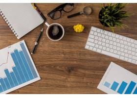 带增长图表和键盘的办公桌俯视图_11383352