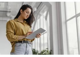 年轻女商人用拷贝空间检查她的平板电脑_12142775