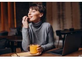 年轻女子在电脑前工作喝着热茶_13376857