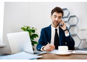 年轻成功的商人在电话里讲话有办公室背景_7855213