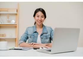 年轻漂亮的亚洲女子微笑着在家中客厅的办公_4395096