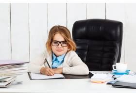 年轻漂亮的女孩坐在办公室的工作场所_7851074