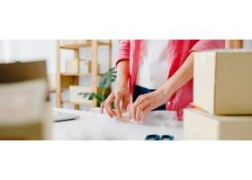 年轻的亚洲企业家女商人将产品装在纸箱里送_10074979