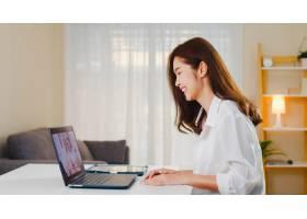 年轻的亚洲商界女性在客厅里工作的同时使_10075834
