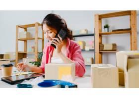年轻的亚洲女商人使用手机接收采购订单并查_10075005