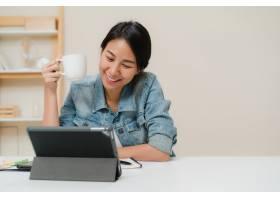 年轻的亚洲女性一边工作一边使用平板电脑_4395103