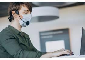 在录音棚工作的妇女戴着口罩_12804203
