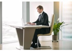 在现代办公桌前用笔记本电脑工作的商人_3938243