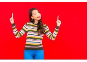 在红色隔离墙上用行动描绘美丽的亚洲年轻女_12045141