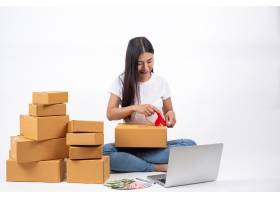 在网上销售中包装包装盒的快乐女性在线工作_4283077