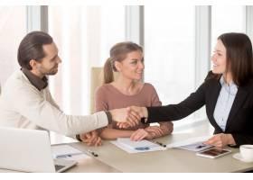 坐在办公室里的商人和女商人在商务会议上握_3938504