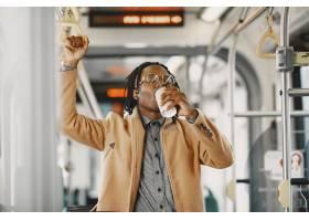 坐在城市公交车上的非裔美国人穿棕色外套_13274715