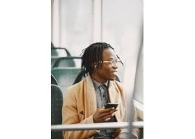 坐在城市公交车上的非裔美国人穿棕色外套_13274729