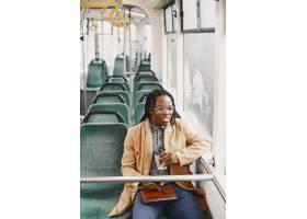 坐在城市公交车上的非裔美国人穿棕色外套_13274732