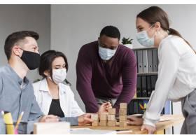 大流行期间人们戴着口罩在办公室开会_10070473