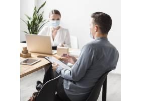 大流行期间在办公室工作的人戴着医用口罩_10070521