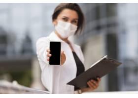 大流行期间在户外工作的妇女拿着记事本展示_10070669