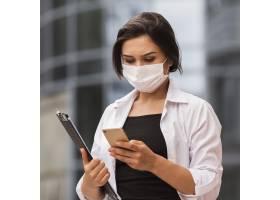 大流行期间女性在户外工作手持智能手机_10070670